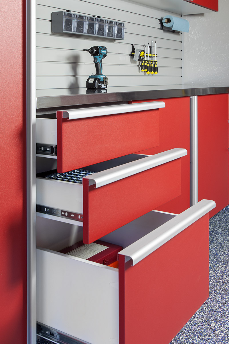 Soft close drawer slides and red powder coating take this custom tool chest to the next level. Backed with slatwall storage, these garage cabinets and stainless steel countertop make the perfect work bench.