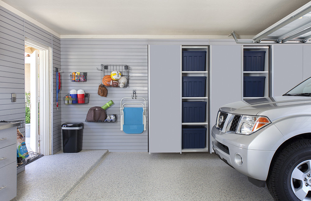Our wall mounted garage cabinets make it easy to keep your garage clean and organized. Off-the-floor storage prevents exposure to moisture, pests and debris. Pictured: Dove grey garage cabinets with custom slatwall storage.