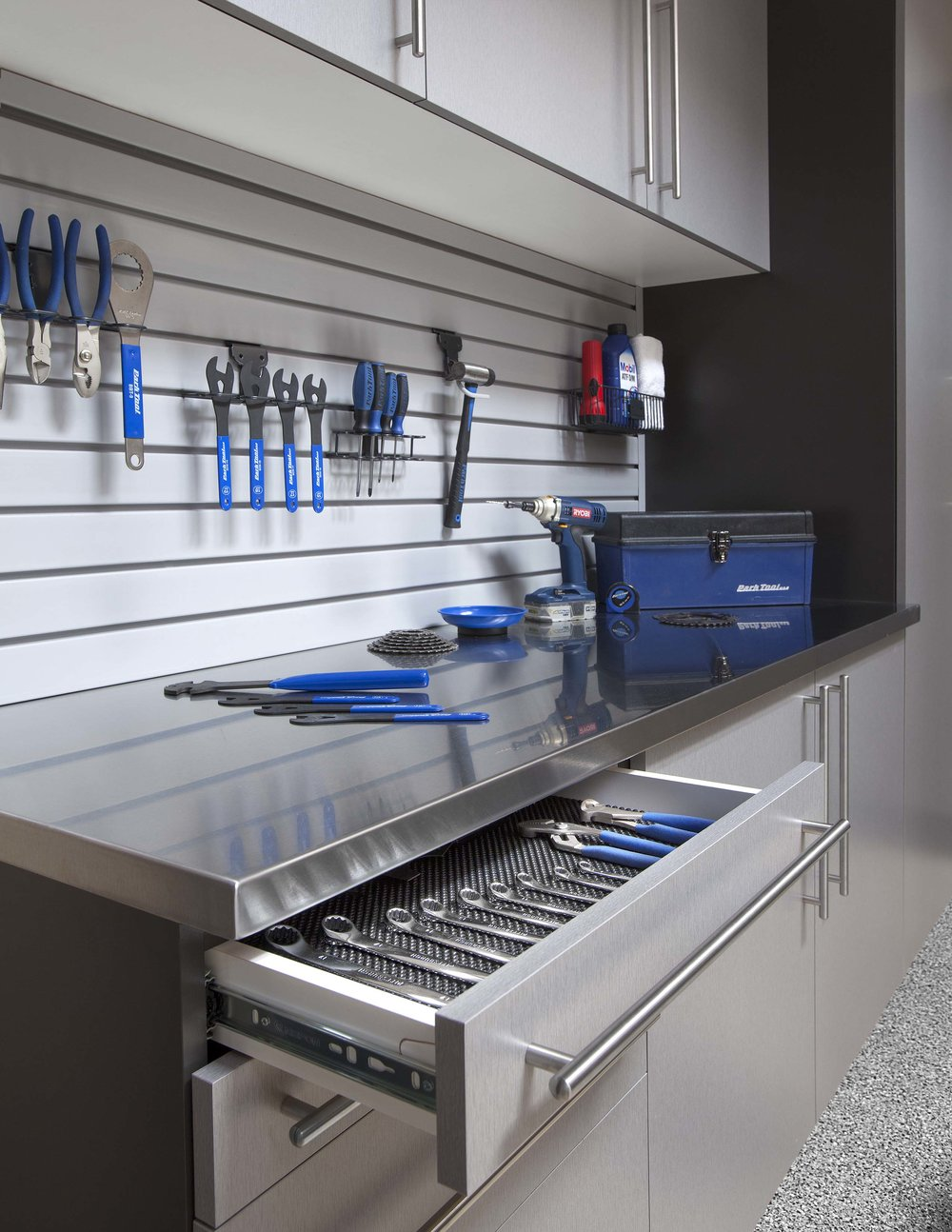 Protect valuable tools and equipment with custom tool storage. Pictured: Dove grey garage cabinets with custom drawer pulls, stainless steel countertop, slatwall storage and custom tool chest.