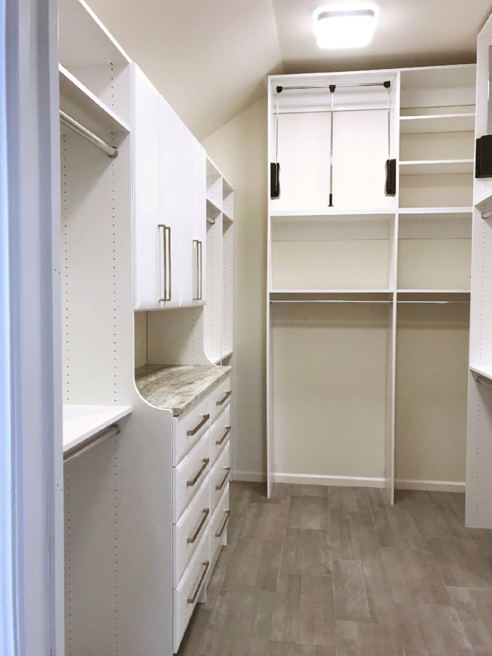 Custom closet shelving maximizes vertical storage in this vaulted master closet by Closets of Tulsa.  Call Closets of Tulsa  today for your FREE consultation and 3-D closet and garage design:  918.609.0214