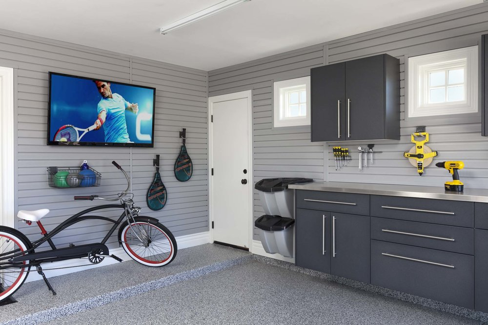 Wall mounted graphite cabinets, upgraded drawer hardware and stainless countertops make this garage storage design feel like another room in the house. Continuous slatwall panels maximize convenience and keep clutter at bay.