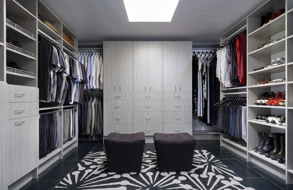 This streamlined custom closet design features a wall of drawers and cabinets so there's plenty of storage behind closed doors.  Call Closets of Tulsa  for your FREE consultation and 3-D closet design:  918.609.0214