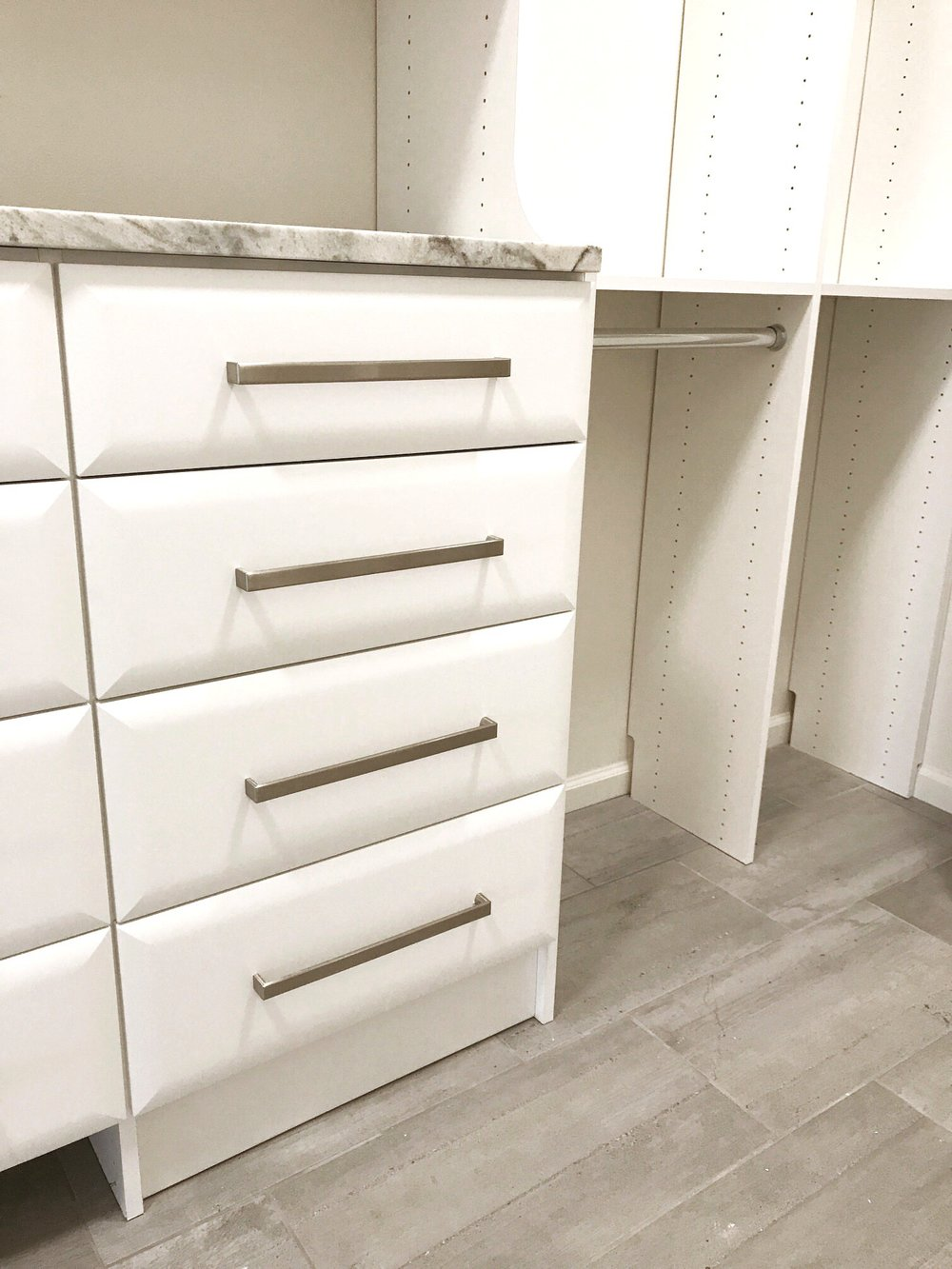 Chic pillow top drawer fronts and upgraded hardware seamlessly blend custom closet drawers by Closets of Tulsa into our client's new custom home.