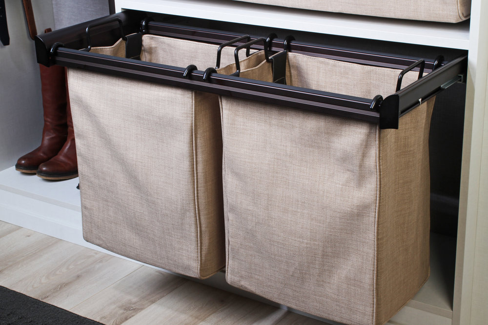 Pullout removable hampers from Closets of Tulsa make laundry days easier.