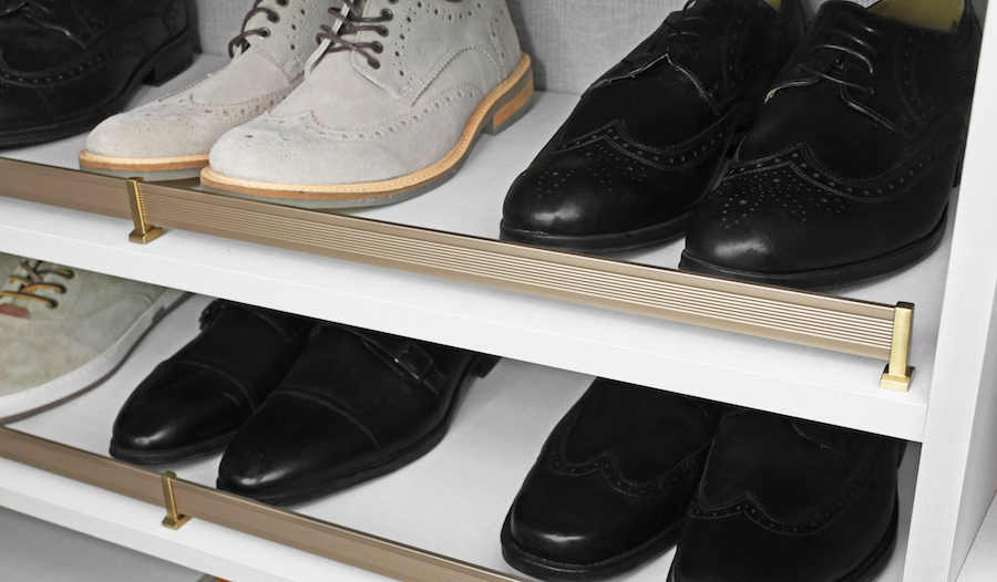 A matte gold shoe fence from Closets of Tulsa keeps your closet shoe rack tidy and stylish.