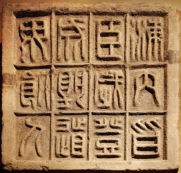 """""""CMOC Treasures of Ancient China exhibit - stone slab with twelve small seal characters, The 12 characters on this slab of floor brick affirm that it is an auspicious moment for the First Emperor to ascend the throne, as the country is united and no men will be dying along the road @ Ayelie, 2007, CC-BY-SA-2.5"""
