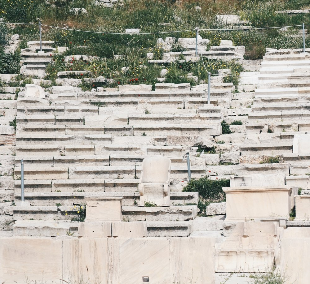 "Phang Zi Xin  ""VIP Seats At Theatre of Dionysus"" , 22 March 2018. A picture of the VIP seats at the Theatre of Dionysus. At the center of the picture, there is a marble chair with back support, and the rows of seats towards the background there are foliage growing."