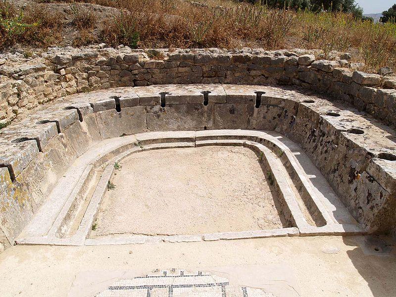 "Profburp.  Dougga latrines cyclopes .  June 2006. Public latrine in a ""C"" shape with multiple seats."