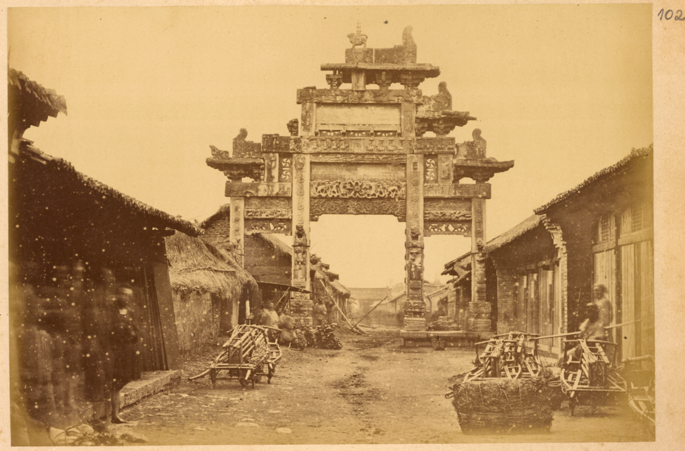 Fae, Ornamental Gateway (Pailou) from Han Dynasty (202 BCE - 220 CE)  Across a Street Lined with Small Shops  (1 March 2014). Public Domain. Alt Text: Faded yellow photo of an ornamental gateway across a street lined with small shops in the Han Dynasty