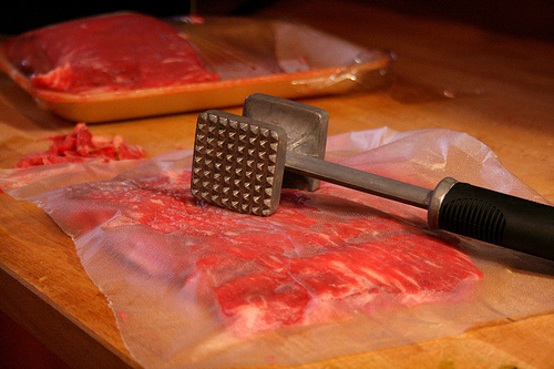 raw meat with mallet