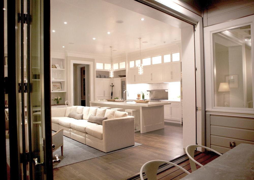 living room, kitchen, open floor plan, hardwood floors, white kitchen, pendants, marble counters, built in shelving, cabinetry