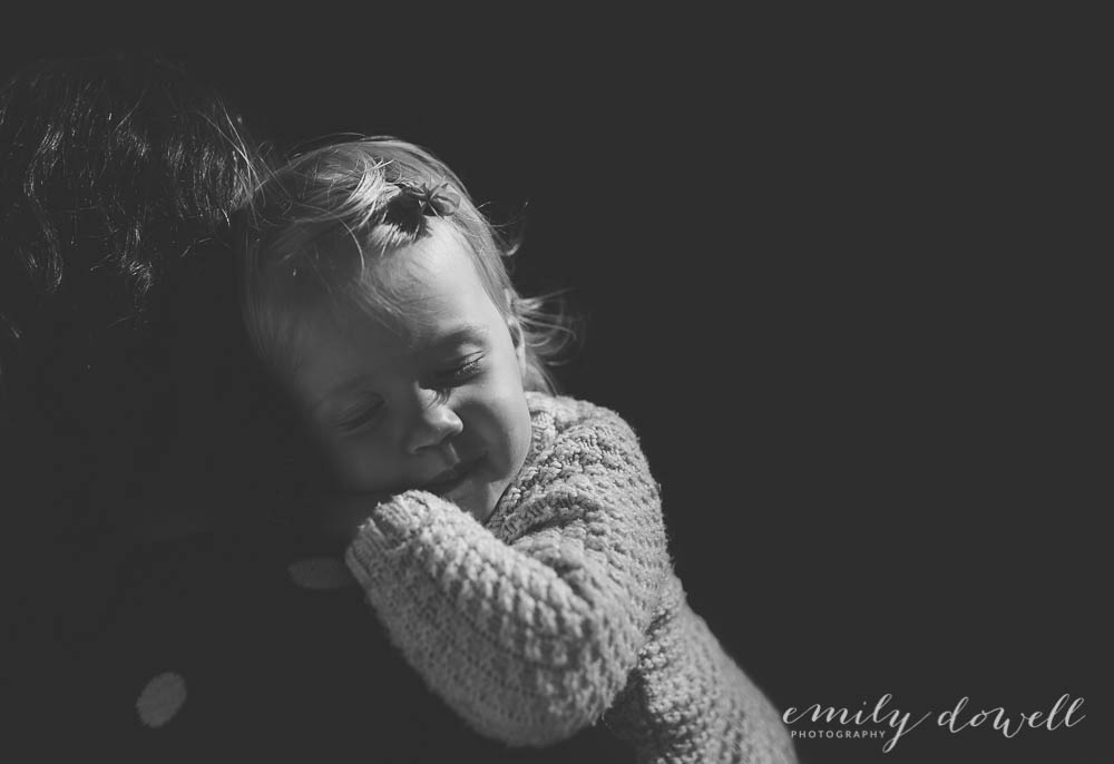 black and white of sleeping child on mother's shoulder