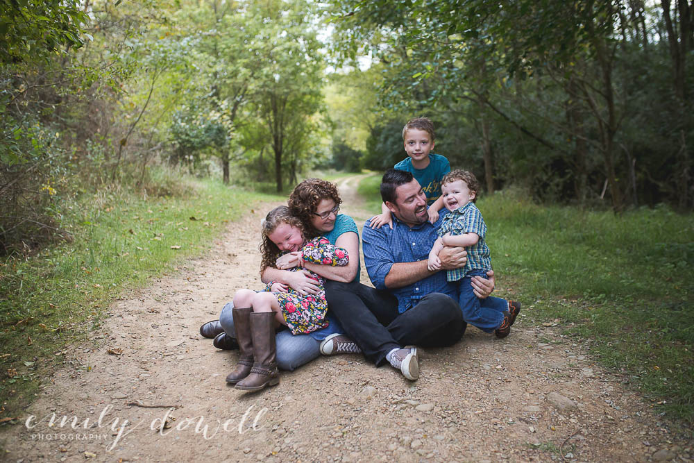 family portrait on trail in woods with laughing children