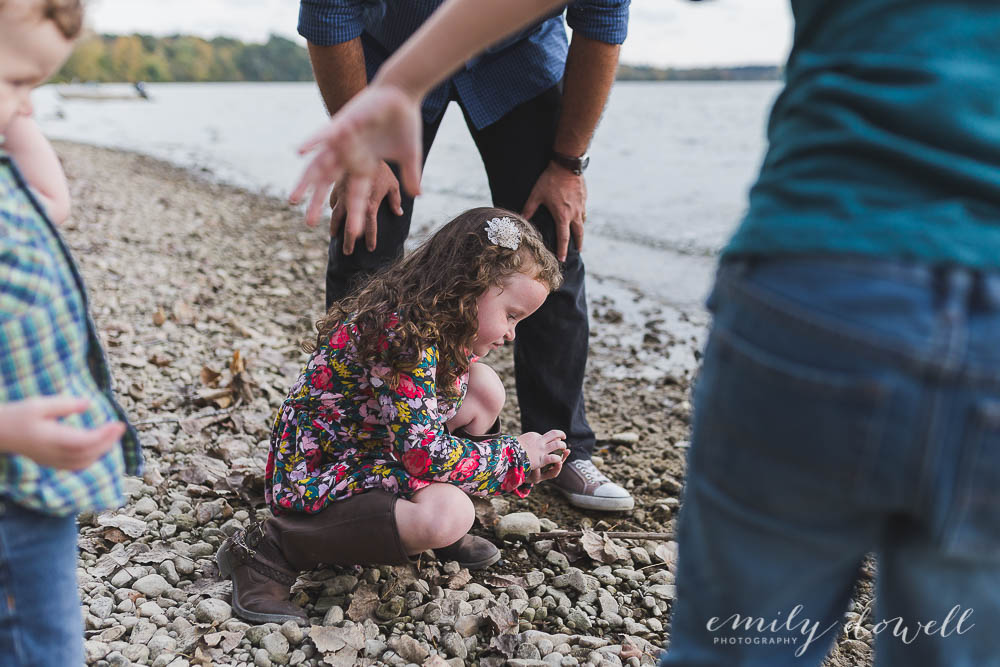 candid image of a girl with her family on the shoreline pickup up rocks