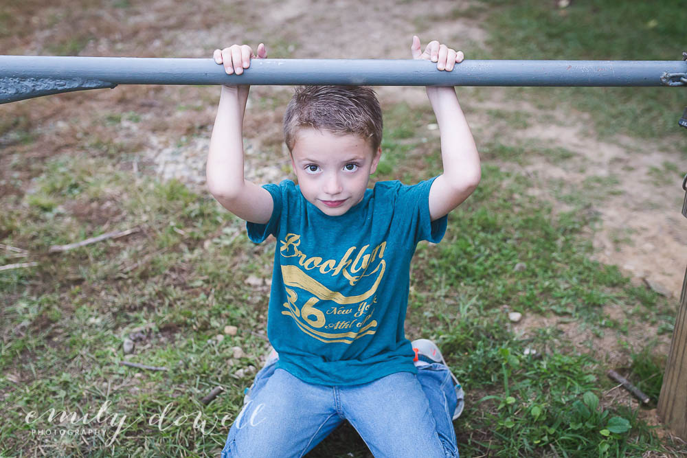 Portrait of a boy ducking under a pole