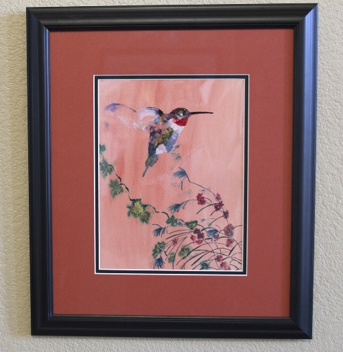 A mixed media piece of watercolors and inks, acetate and watercolor paper. I painted the hummingbird using alcohol inks on a clear acetate and overlaid it on top of a floral watercolor and India ink painting.