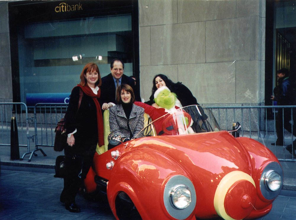 "A 20th anniversary celebration would be incomplete without recognizing our longtime friends and clients at Neiman Marcus. Pictured here in 2001 at the Today Show with a featured gift in the renowned Neiman Marcus Christmas Book are CEO Tom Goodman with NM greats Ginger Reeder and Karen Katz, along with former GMI star Jane Lehman! ""The Grinch"" is seated in Martha Whovier's Grinch Roadster from the film ""The Grinch That Stole Christmas."""