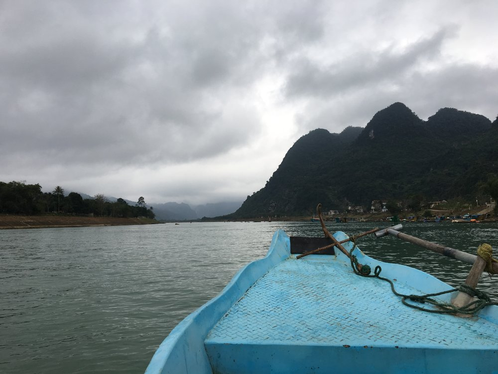 Turquoise boat on a teal river through an emerald green valley