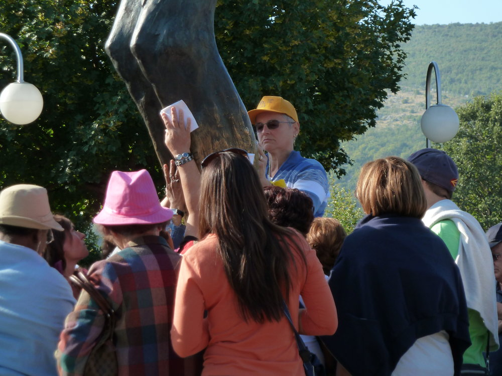 """Tourists examining the """"weeping knee"""" of the Risen Christ statue, Medugorje, Hercegovina"""