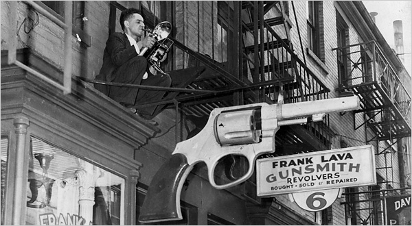 Weegee perched on a fire escape, New York. Photo by Leigh Wiener.