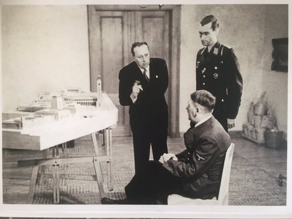 Hitler (seated) admires the plans for Linz alongside his architect, Herman Gisler (left)