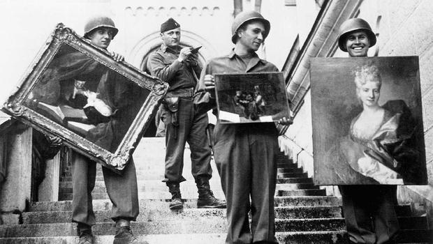 American GIs, under the supervision of Capt. James Rorimer, carry paintings down the steps of Neuschwanstein Castle in southern Germany. Courtesy National Archives and Records Administration