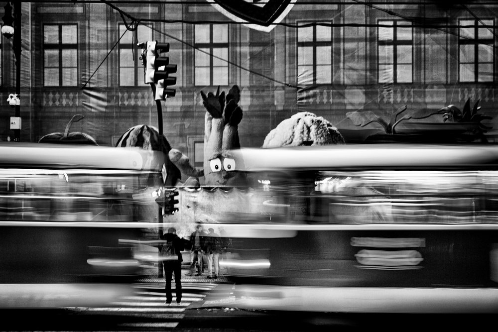 Crossing. Prague, October 2016.  Waited some time for this. I was really taken by the huge toy vegetables (I think) on this construction site and wanted a picture with the tiny real people captured below. Timing with the tram was less straightforward.