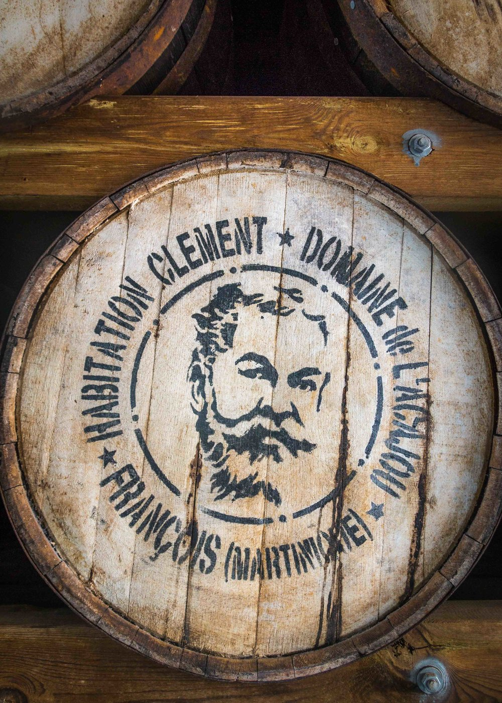 A barrel of aging rum features a portrait of Charles Clément