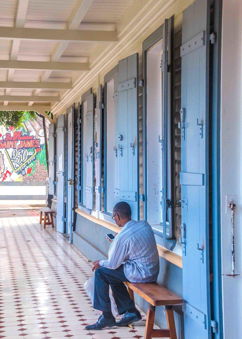 martinique, distillerie saint-james : homme assis sur veranda