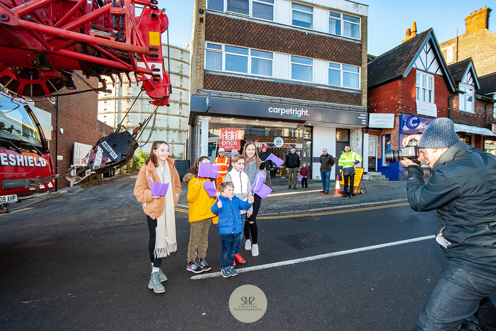 Local children pose for photographs waving purple Oxted Regen flags to witness the arrival of the crane.