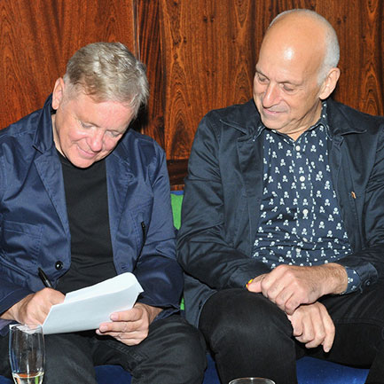 New Order's Bernard Sumner signs on the dotted line. Daniel Miller looks on.