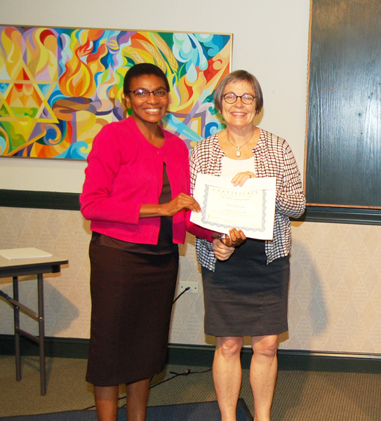 Funmi Kehinde (left) receives a certificate from seminar leader Harriet Hill.