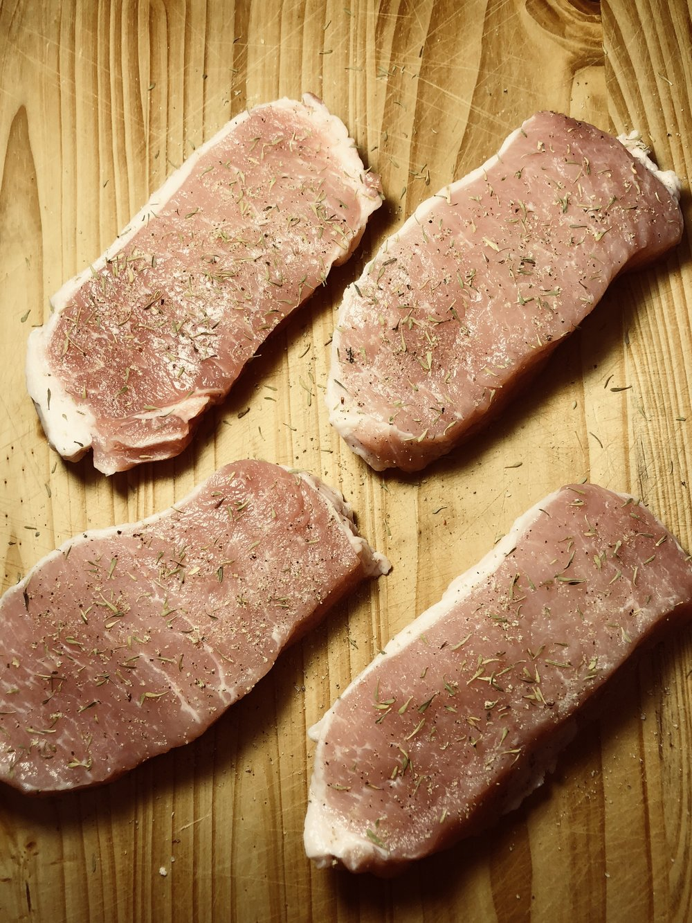 Pork chops seasoned with salt, pepper and thyme.