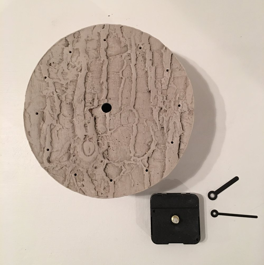 Wall hanging clock with impressed tree bark motif.
