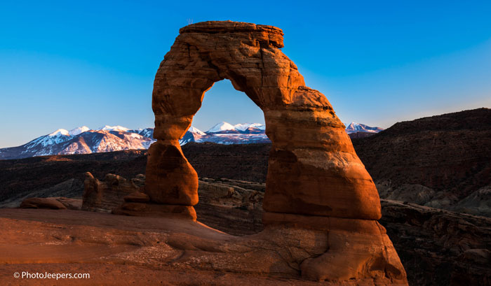 Delicate-Arch-Arches-National-Park-sunset-winter-snow-mountains-Photo-Jeepers.jpg