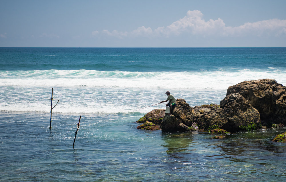 A genuine fisherman fishing from a small rocky island close to shore