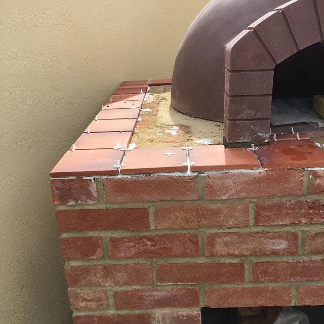 Putting the glazed tiles around the pizza oven #tiles#pizzaoven #gardencooking #