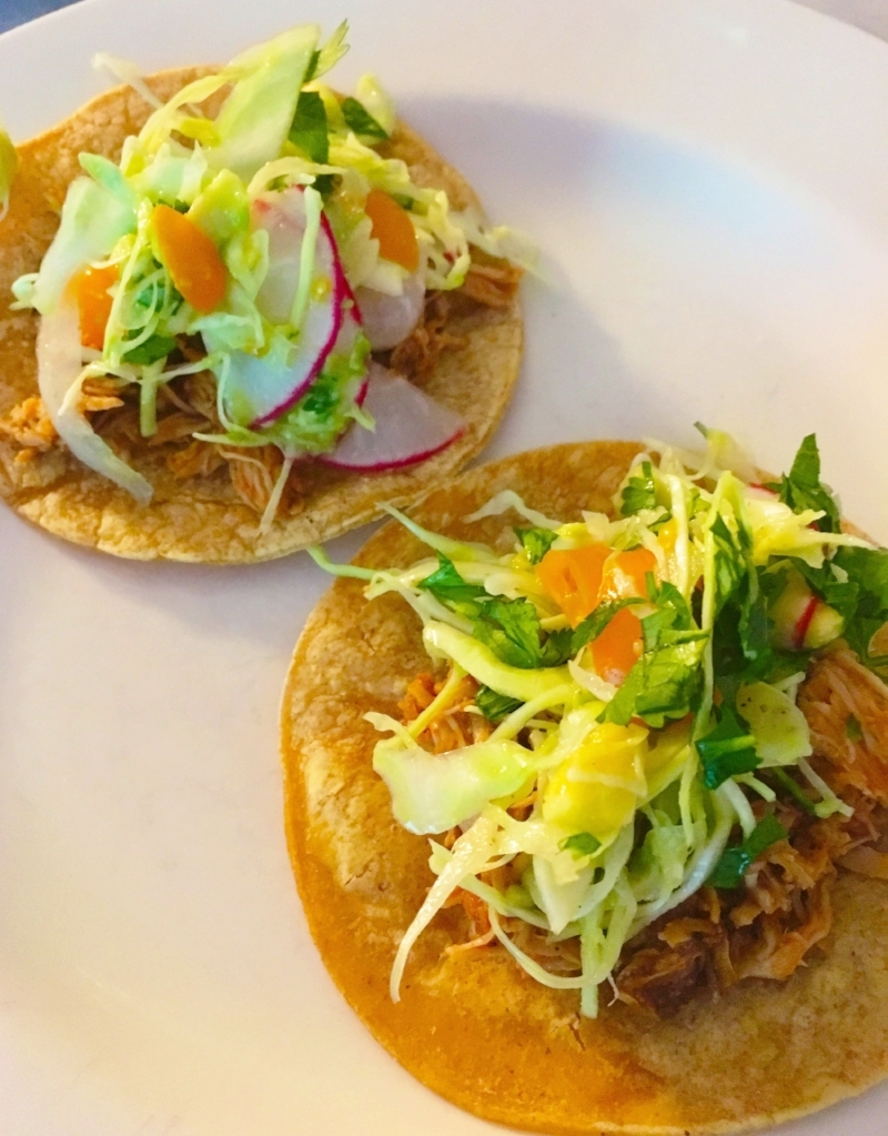 Warm the corn tortilla, load with shredded chicken. Top with slaw. Enjoy!
