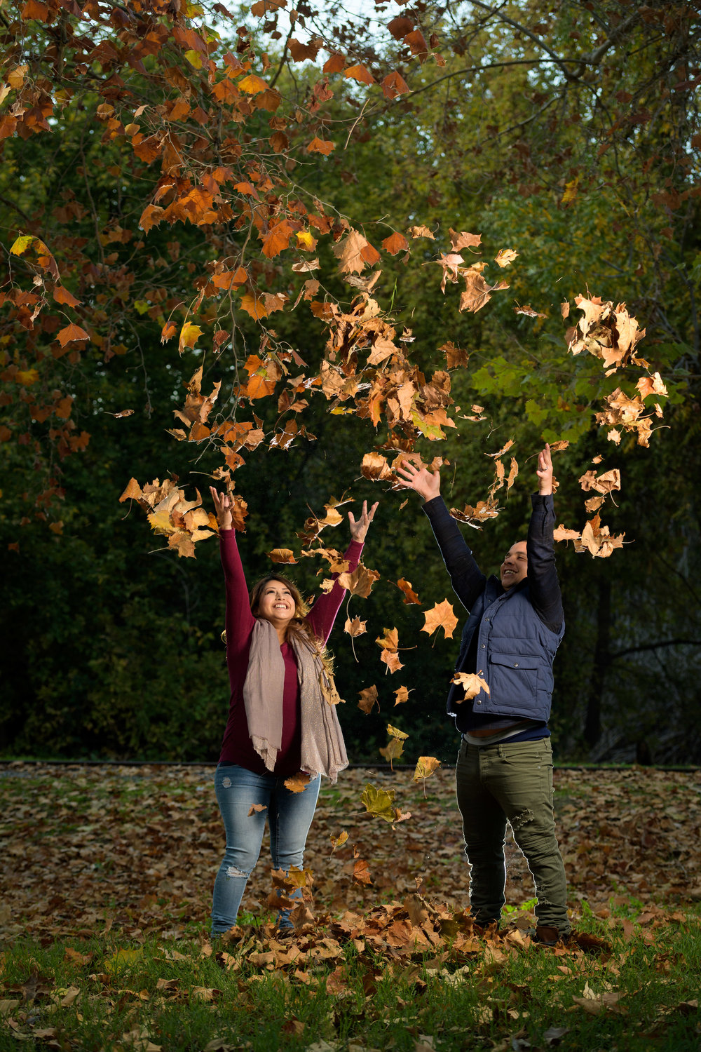Throwing fall leaves in the air - Vasona Park Maternity Photography – by Bay Area portrait photographer Chris Schmauch