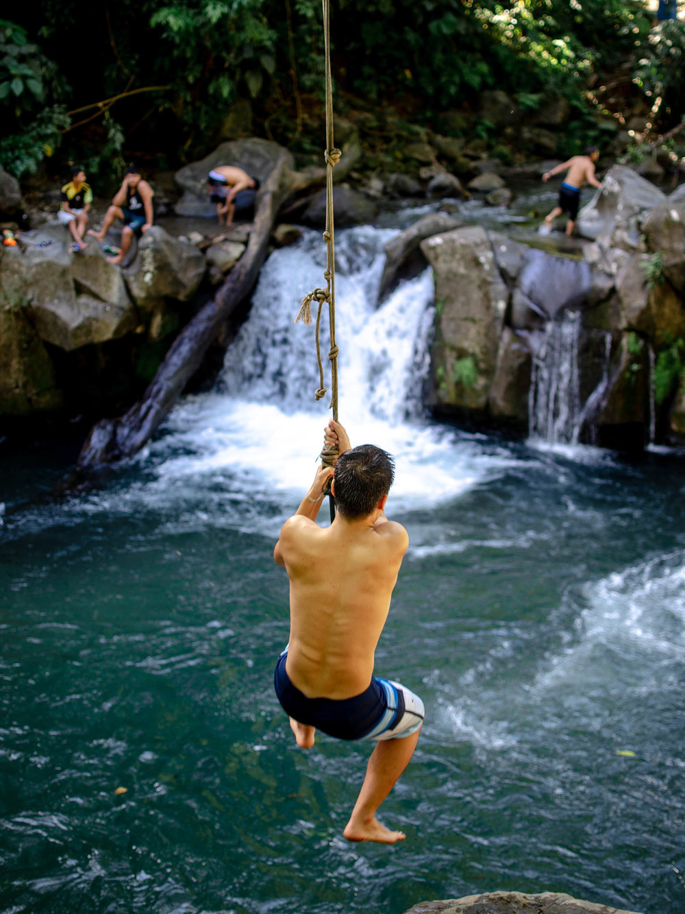 Swinging off a rope swing into El Salto in La Fortuna