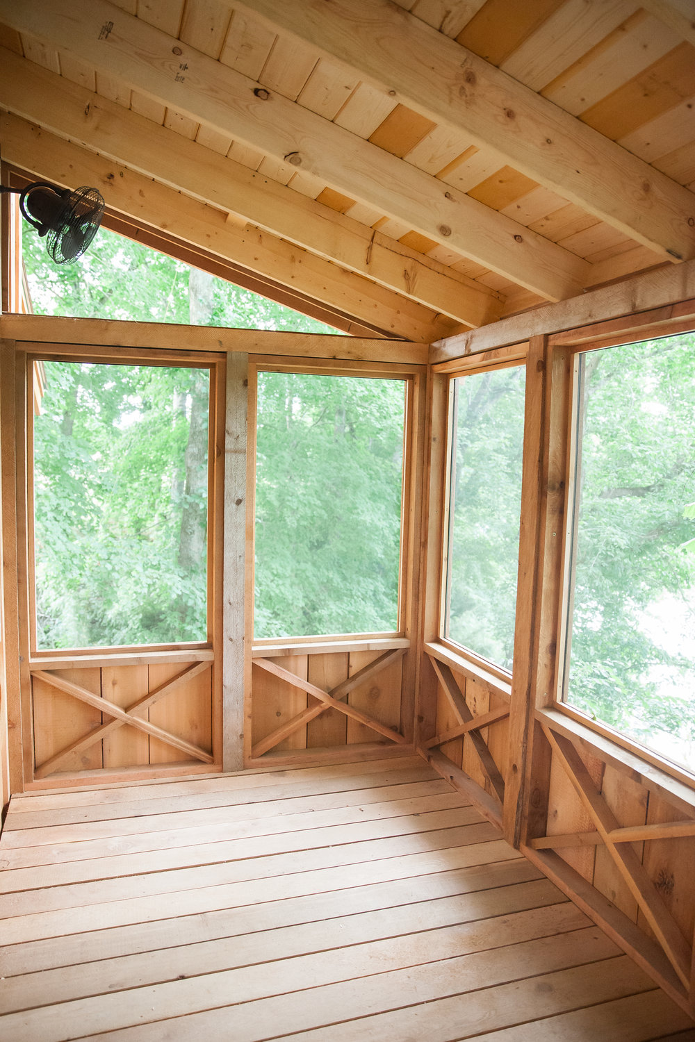 The screened-in porch hangs directly above the river.