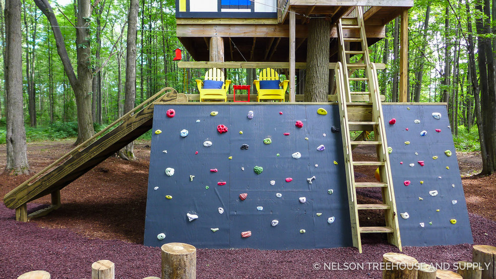 The crew enlarged the first platform to add more space for play, and added the rock wall and slide for extra adventurous entrances & exits. The ladder is a classic Nelson Treehouse ship ladder. You can find plans to make your own at store.beinatree.com!