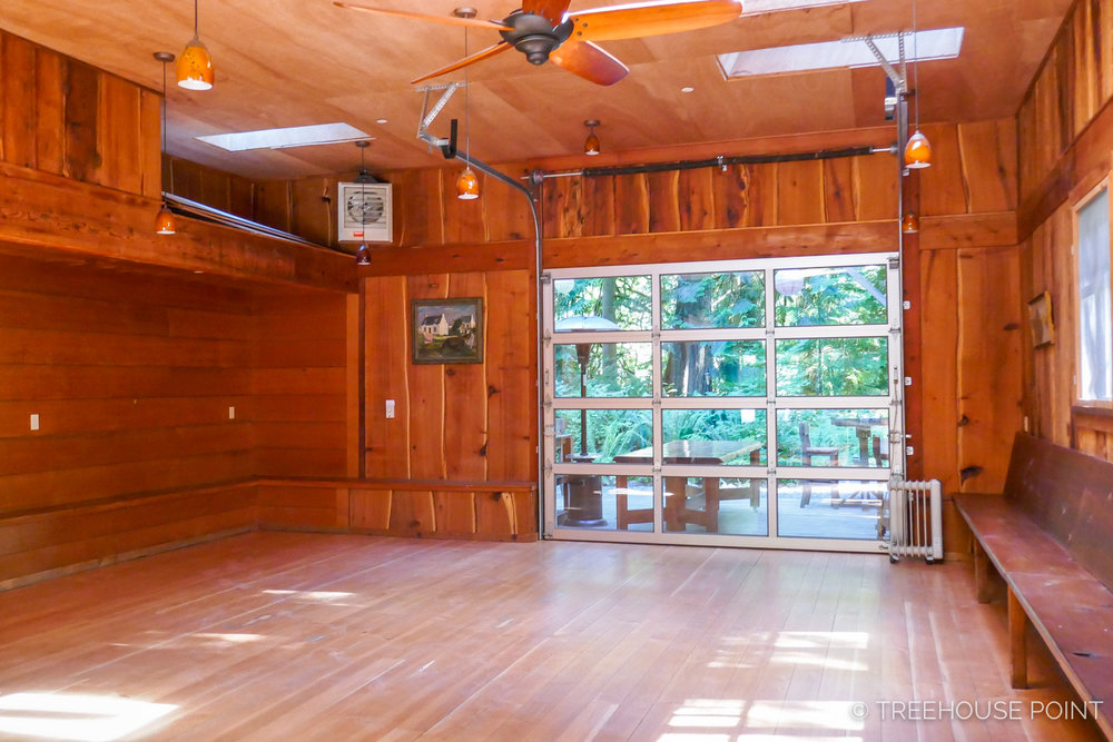 the RETRACTABLE window wall at the back of the room Opens to the forest.