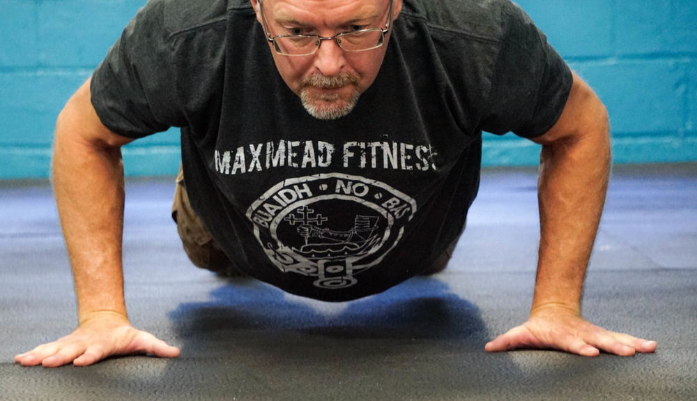 This picture shows a man doing a pushup during a  Maxmead Fitness, CrossFit, Strength & Conditioning workout or WOD.