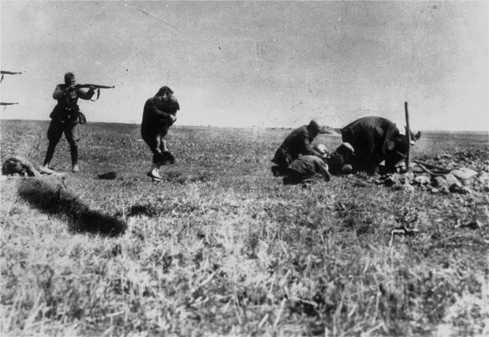 A photo of a member of the Einsatzgruppen about to execute a Ukranian woman and her infant child in 1941.