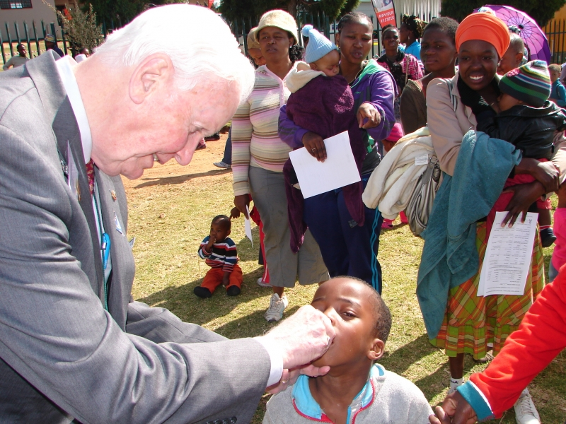 7-chairman-of-the-rotary-foundation-mr-wilf-wilkinson-administers-polio-drops-to-a-child-in-south-africa.jpg