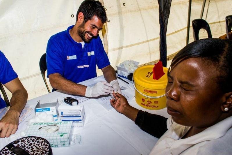 12-a-medical-volunteer-administers-a-pinprick-blood-test-as-patient-cringes.jpg