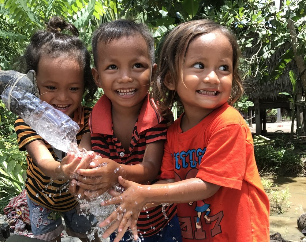 Children enjoy the water a new well provides in Svay Rieng Provence, Cambodia