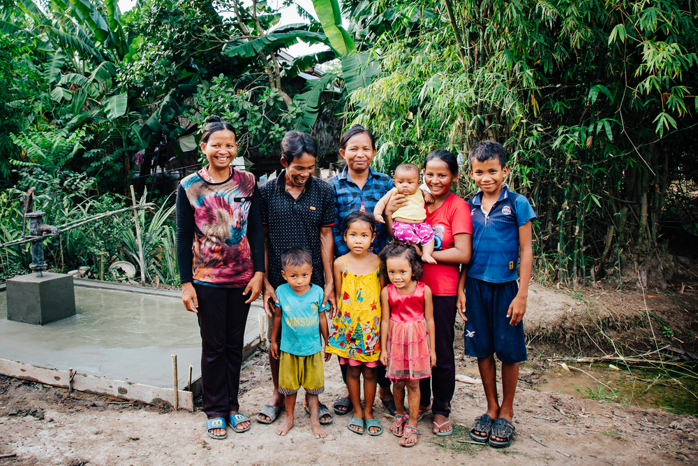 An excited family in Svya Rieng Province, standing in front of their new well!