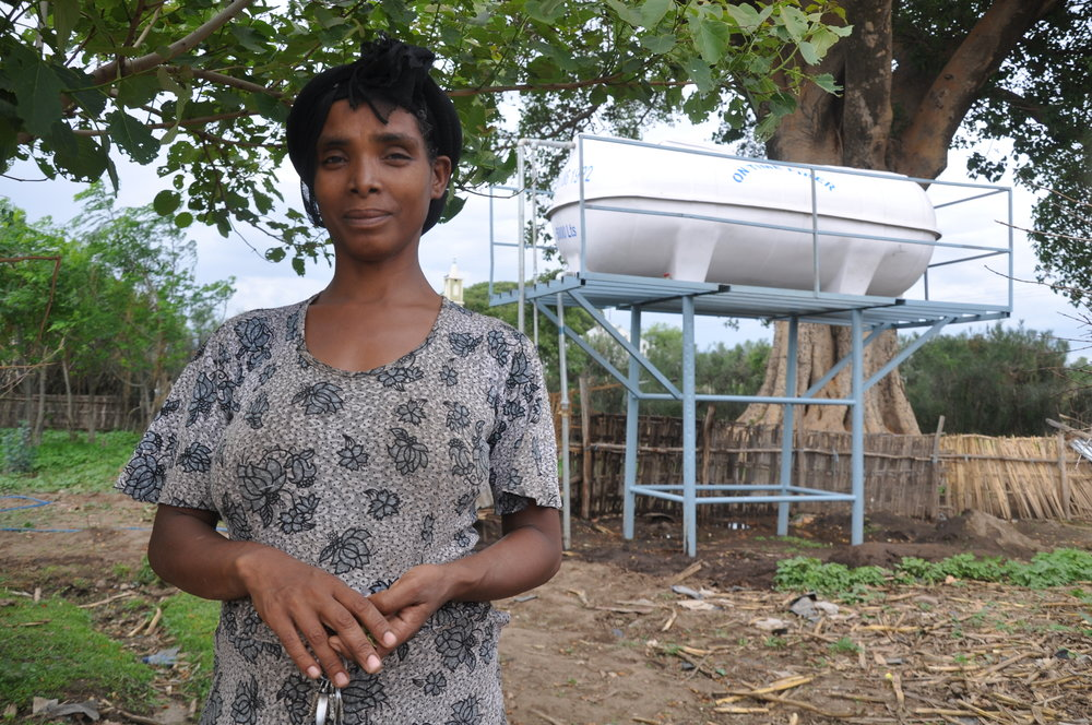 (Fig. 1) Mammay next to the new water tank filled by a solar powered pump.